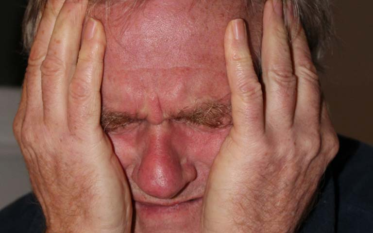 a man suffering from severe dental pain