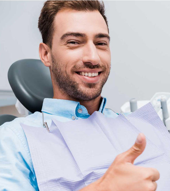 Satisfied middle-aged man in a dental chair showing his thumb up.