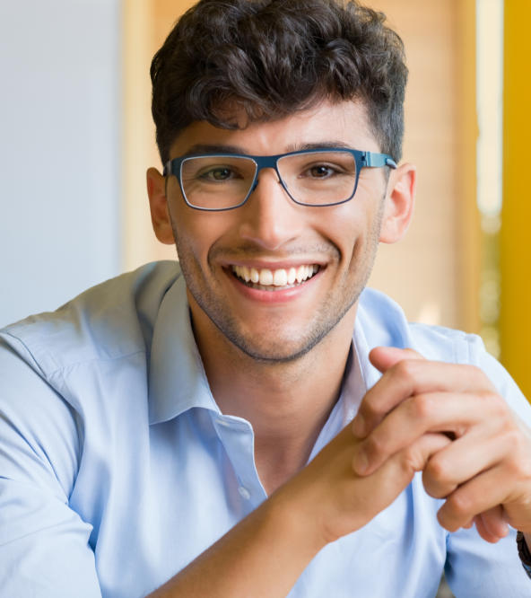 Cheerful man with glasses showing perfect teeth in his smile.