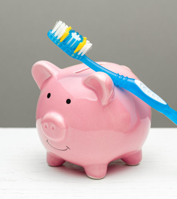 A toothbrush leaning on a piggy money-bank.