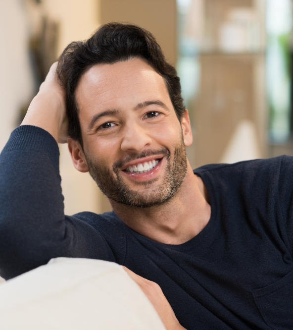 Cheerful man sitting on a sofa showing healthy teeth in his smile.