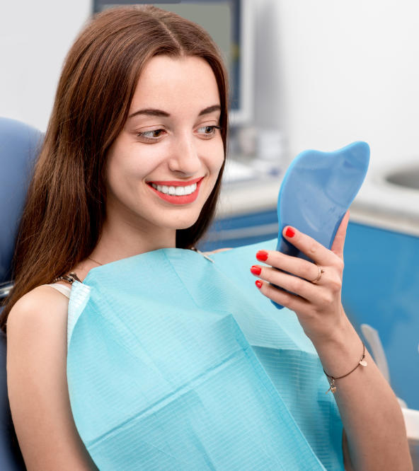 Young woman in a dental chair after treatment watching her nice teeth in a mirror.