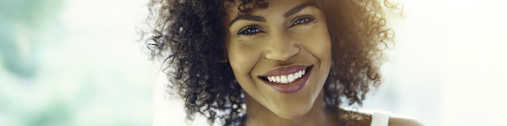 Happy Afro-American woman showing her perfect teeth in a smile.