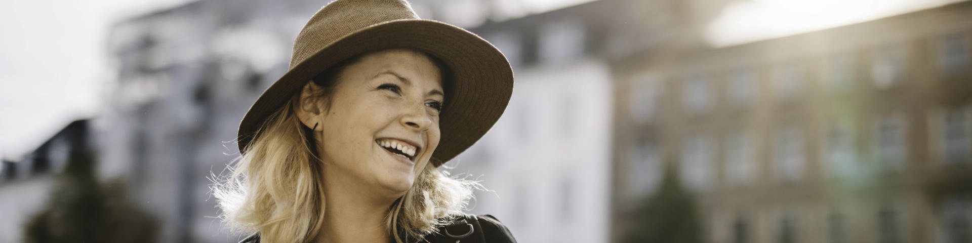 Cheerful broadly smiling woman wearing a hat.