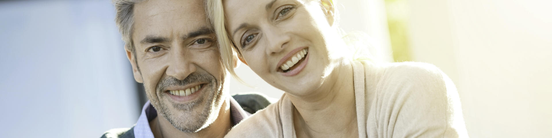 Happy middle-aged couple showing perfect teeth in their smiles.