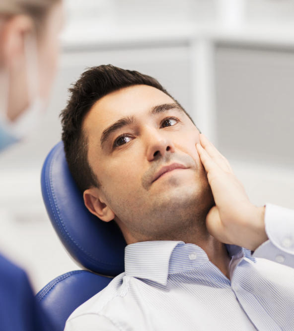 Man with severe dental pain in a dental talking to a dentist.