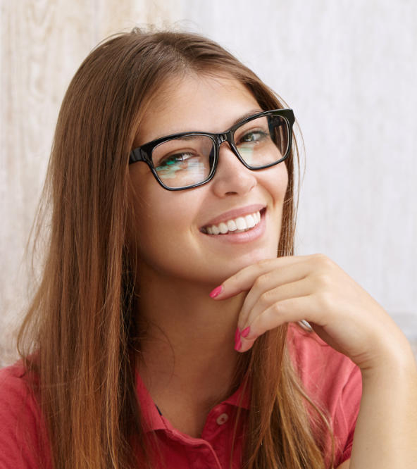 Young woman with glasses showing perfect teeth in her smile.