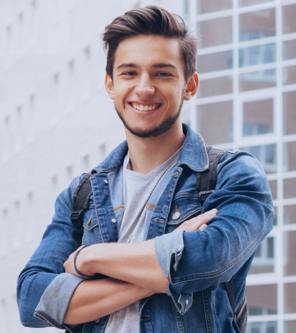 Joyful young man showing nice teeth in his smile standing in front of an office building.