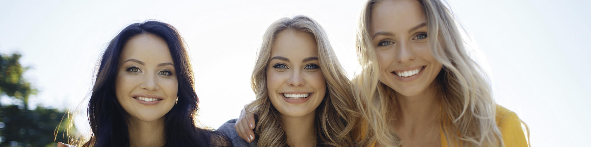 Three young woman with perfect smiles.