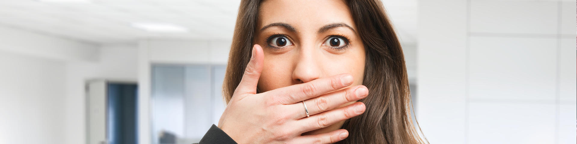 Young confused woman covering her mouth due to bad breath.