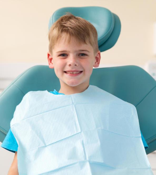 Smiling boy in a dental chair after pediatric dental treatment.