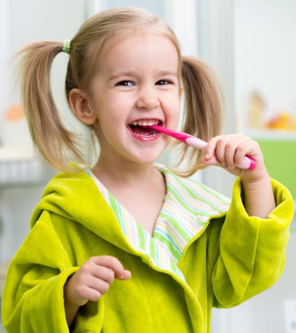 Little happy girl brushing her teeth.
