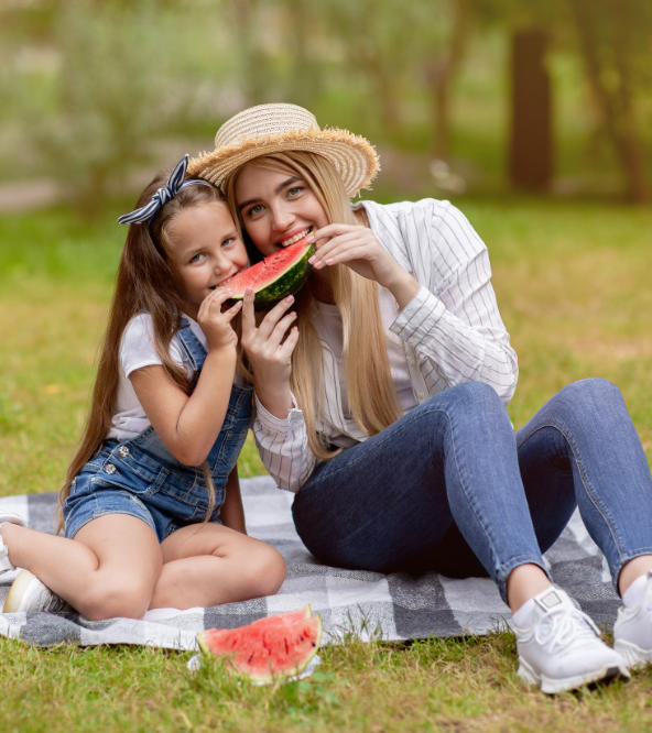 Happy mother with her daughter eating water melon at the picnic.