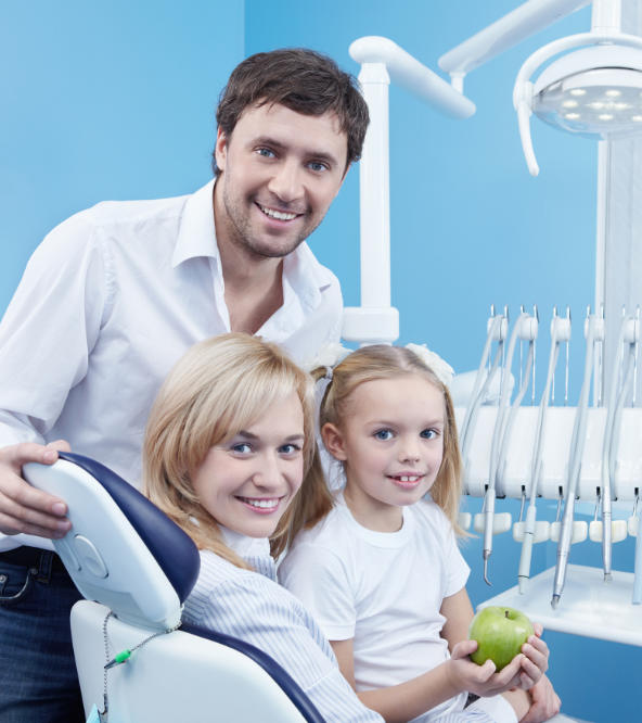 A girl holding a green apple with her parents at dentistry office.
