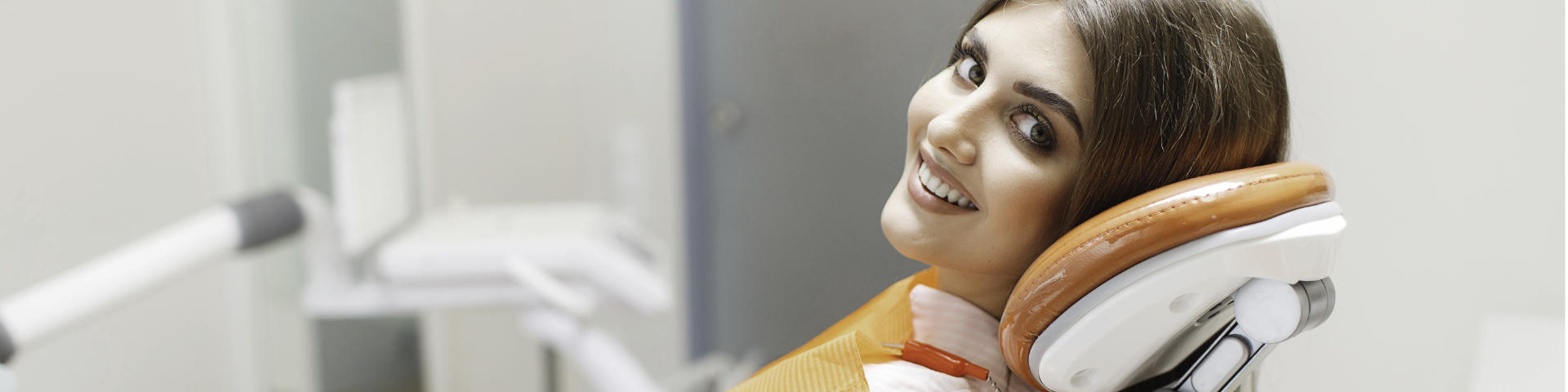 Satisfied young woman with perfect smile in a dental chair.
