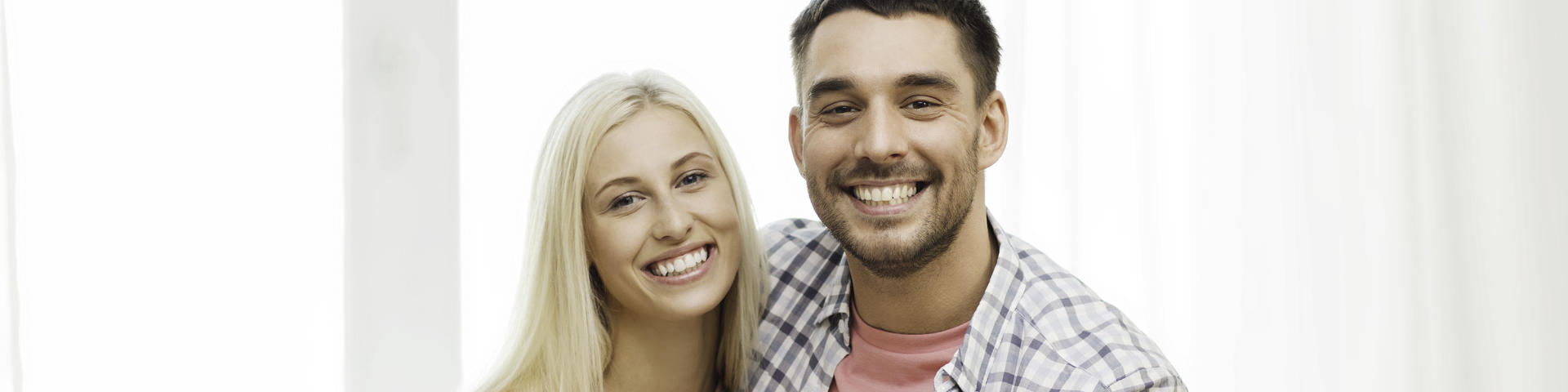 Young couple showing healthy nice teeth in their smiles.