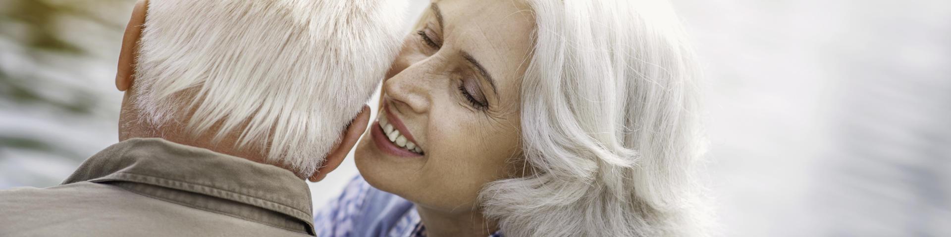 Joyful elderly woman whispering to her husband's ear.