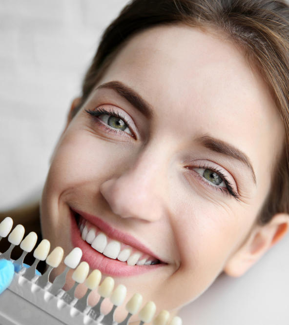 Dentist matching veneers color with woman's natural teeth color.